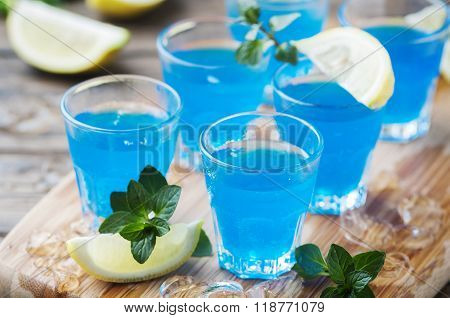Blue Curacao Liqueur With Lemon On The Wooden Table