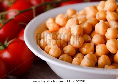 Detail Of Chickpeas In White Bowl Next To Several Tomatoes