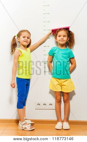 Two girls standing by the scale on the wall and fixating the height with book looking at camera and smiling in full height portrait