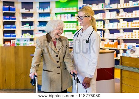 Senior Woman And Doctor Laughing In Pharmacy