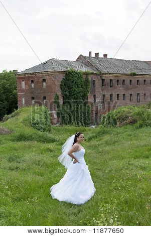 Young bride posing for the camera with large castle behind her