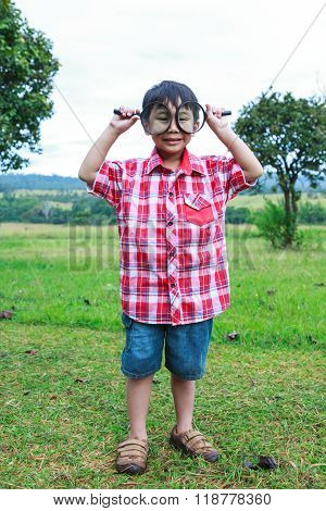 Full Body. Young Boy Exploring Nature With Magnifying Glass. Outdoors.