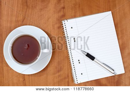 Notepad And A Cup Of Tea On Wooden Table From Abov