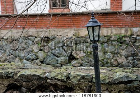 Crooked street lamp in front of a brick building