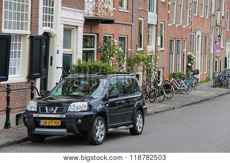 Parking Car And Bicycles Near Old Buildings In The Historic Centre Of Haarlem, The Netherlands