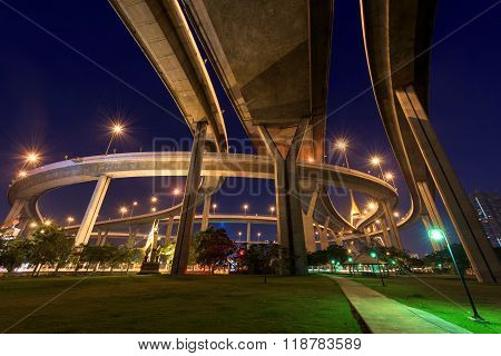 Bhumibol Bridge above park at dawn in Bangkok Thailand. Foreign text on the bridge is the bridge name