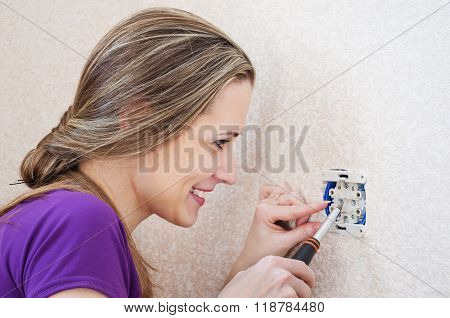Woman Makes Repairs To Electrical Socket