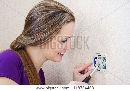 Woman With A Smile Makes Repairs Electrical Outlet