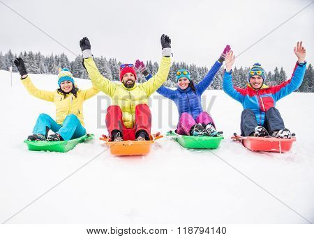 Friends Riding Snow Sleds