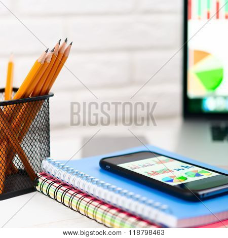 Workplace with notebook , laptop, pencils on a light background.