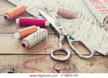 Scissors, bobbins with thread and needles, striped fabric. Old sewing tools on the old wooden backgr