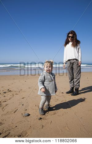 Baby And Mother In Beach Looking At Camera