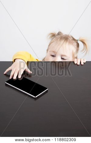 Baby Trying To Catch Phone On Table