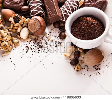 Roasted coffee beans, chocolate, candy, nuts, cup and the place for inscriptions on white background