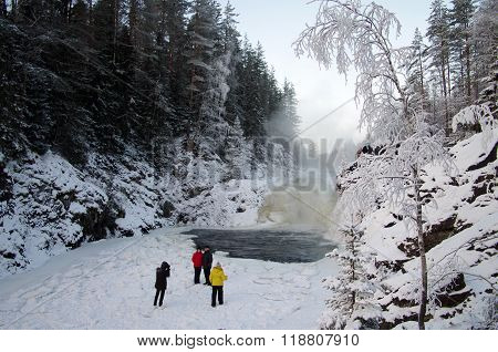 Karelia, Russia - January, 2016: People Are Photographed On The Background Waterfall Kivach In Cloud