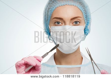 Portrait Of Female Surgeon Wearing Surgical Scrubs, Gloves And A Scrub Cap, Holding A Surgical Scalp