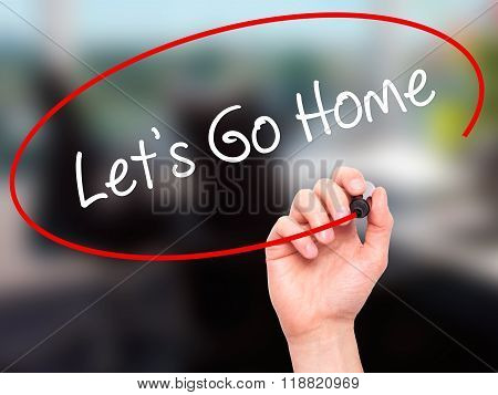 Man Hand Writing Let's Go Home With Black Marker On Visual Screen