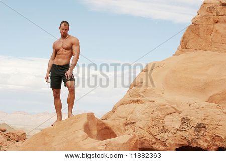 Hombre musculoso guapo en rocas rojas