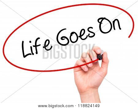 Man Hand Writing Life Goes On With Black Marker On Visual Screen
