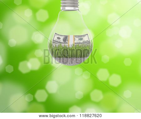 Light bulb with grass and a wad of dollars inside on green background