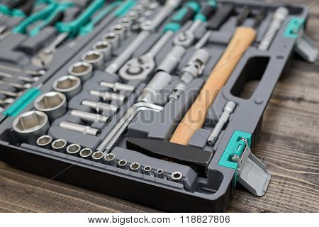 Open black toolbox with different instruments on wooden surface