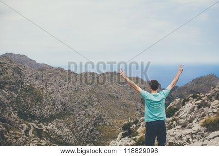 Young man standing on cliff with hands raised
