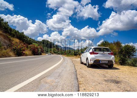 PALEOCHORA, CRETE, GREECE - AUGUST 2015: White Toyota Auris stays parked among clouds on road of Crete island.