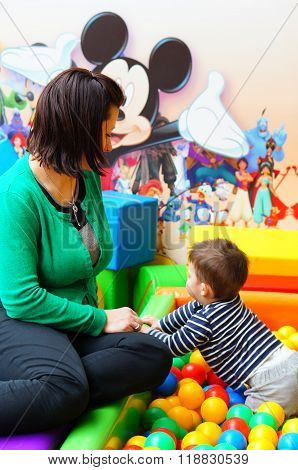POZNAN POLAND - FEBRUARY 20 2016: Mother sitting by two years old boy in a play room