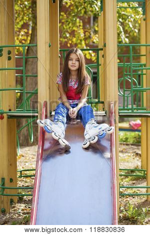 Young girl sitting at the playground in roller skates