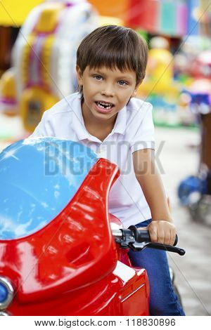 Little boy sitting on a toy red motorcycle in an amusement park