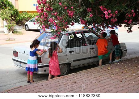 Antalya, Turkey - June 7, 2015: Children Decorate A Parked Car With Oleander Flowers
