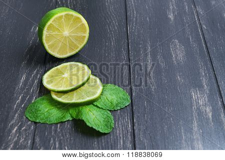 Cut Into Slices Of Lime And Mint Leaves