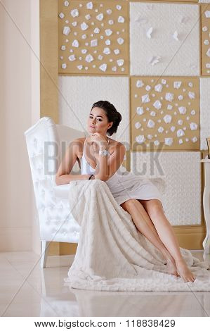 Beautiful woman sitting on a white chair in the hall