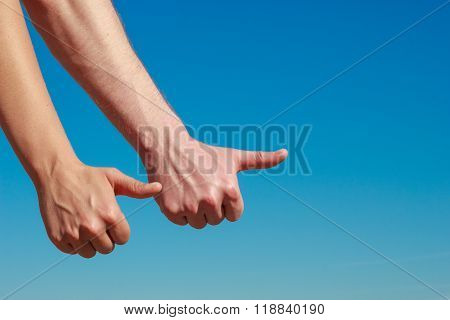 Male Hands Thumbing And Hitch Hiking Outdoor