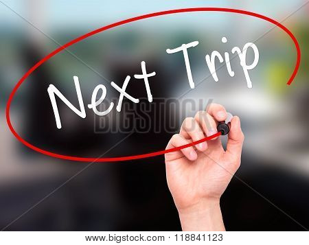 Man Hand Writing Next Trip With Black Marker On Visual Screen