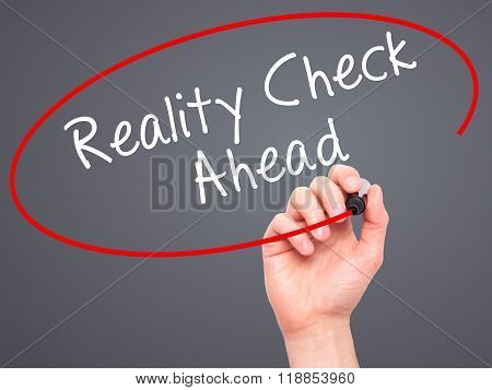 Man Hand Writing Reality Check Ahead With Black Marker On Visual Screen