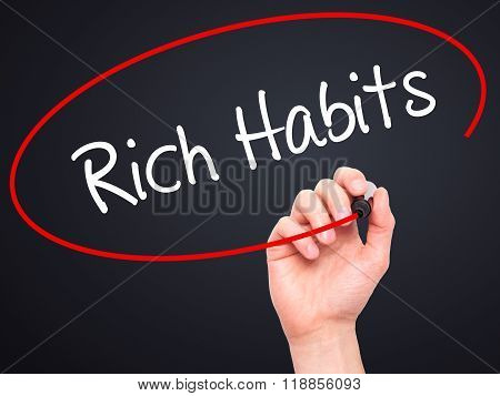 Man Hand Writing Rich Habits With Black Marker On Visual Screen