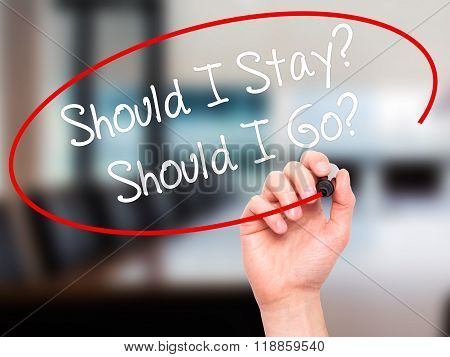 Man Hand Writing Should I Stay? Should I Go? With Black Marker On Visual Screen