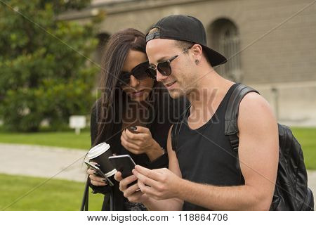 Two cheerful friends taking photos of themselves on smart phone urban city outdoor scene selective focus