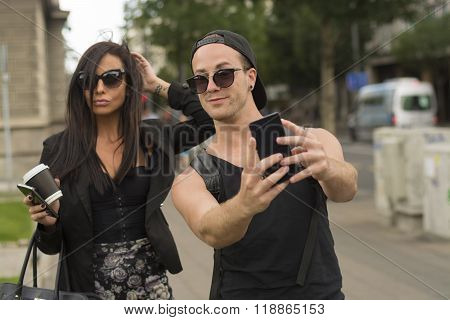 Cheerful friends taking photos of themselves on smart phone urban city outdoor scene selective focus