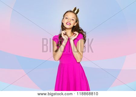 people, holidays and fashion concept - happy young woman or teen girl in pink dress and princess crown over pink violet background