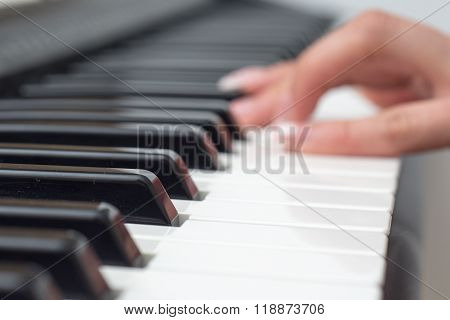 Blurred Woman hand playing MIDI controller keyboard synthesizer close up