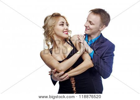 happy young couple dancing, isolated against white studio background