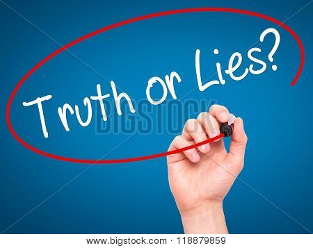 Man Hand Writing Truth Or Lies? With Black Marker On Visual Screen