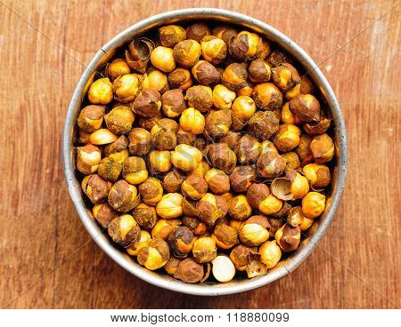 Roasted bengal gram kept on cup on a blurred background
