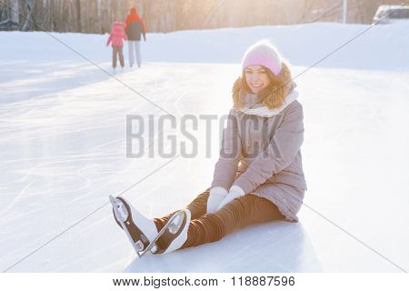 Ice skating woman sitting on the ice smiling