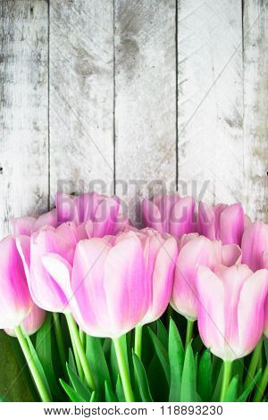Pink tulips over shabby white wooden table