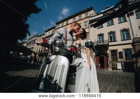 bride and groom on vintage motor scooter
