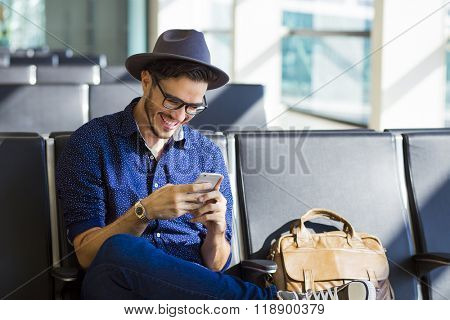 Young traveler on an airport, with a leather jacket laughing with his smartphone