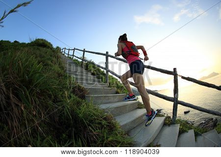 young fitness woman runner running on seaside mountain trail